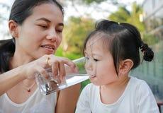 Μητέρα που δίνει το ποτήρι του νερού στο παιδί της στοκ εικόνα