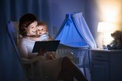 Μητέρα που διαβάζει ένα βιβλίο σε λίγο μωρό Στοκ Φωτογραφία