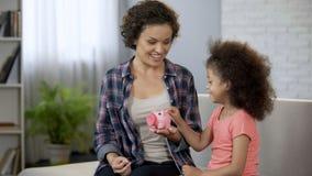 Μητέρα που διδάσκει λίγη κόρη για να κερδίσει χρήματα, που ρίχνουν τα νομίσματα στη piggy τράπεζα στοκ εικόνες