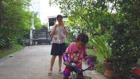 Μητέρα που διδάσκει την κόρη της για να οδηγήσει ένα ποδήλατο απόθεμα βίντεο