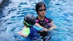 Μητέρα που διδάσκει το αγόρι της για να κολυμπήσει στην πισίνα απόθεμα βίντεο
