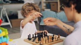 Μητέρα που διδάσκει το χαριτωμένο αγόρι για να παίξει το σκάκι ενώ το παιδί έχει τα κινούμενα κομμάτια διασκέδασης απόθεμα βίντεο