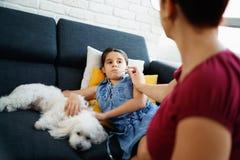 Μητέρα που ελέγχει τη θερμοκρασία στην άρρωστη κόρη με το θερμόμετρο Στοκ Εικόνες
