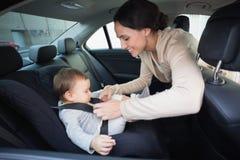 Μητέρα που εξασφαλίζει το μωρό της στο κάθισμα αυτοκινήτων Στοκ εικόνα με δικαίωμα ελεύθερης χρήσης