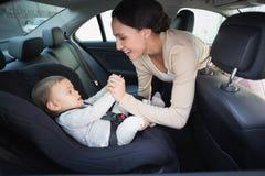 Μητέρα που εξασφαλίζει το μωρό της στο κάθισμα αυτοκινήτων Στοκ εικόνες με δικαίωμα ελεύθερης χρήσης