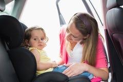 Μητέρα που εξασφαλίζει το μωρό της στο κάθισμα αυτοκινήτων Στοκ Φωτογραφία