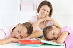 Μητέρα που εξετάζει τα κουρασμένα παιδιά μετά από να κάνει την εργασία Στοκ Φωτογραφίες