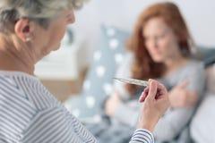 Μητέρα που εξετάζει το θερμόμετρο πυρετού Στοκ εικόνα με δικαίωμα ελεύθερης χρήσης