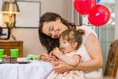 Μητέρα που εξετάζει το κορίτσι γενεθλίων που τρώει Cupcake Στοκ Εικόνες