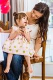 Μητέρα που εξετάζει το κορίτσι γενεθλίων που τρώει Cupcake Στοκ Φωτογραφίες