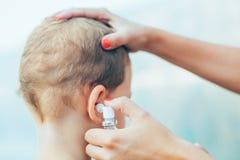 Μητέρα που θεραπεύει τη μόλυνση αυτιών μικρών παιδιών στοκ φωτογραφίες
