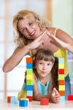 Μητέρα που διαμορφώνει τη μορφή στεγών σπιτιών επάνω από το παιδί Στοκ Φωτογραφίες
