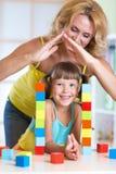 Μητέρα που διαμορφώνει τη μορφή στεγών σπιτιών επάνω από το παιδί Στοκ Εικόνες