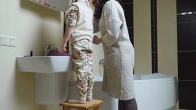 Μητέρα που κάνει makeup μπροστά από τον καθρέφτη στο λουτρό με λίγη κόρη φιλμ μικρού μήκους