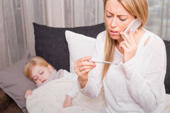 Μητέρα που καλεί το γιατρό και που εξετάζει το θερμόμετρο Στοκ Φωτογραφίες