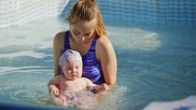Μητέρα που κρατά την κόρη της και αυτή που έχει τη διασκέδαση στην πισίνα φιλμ μικρού μήκους