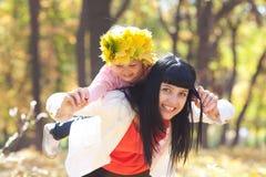 Μητέρα που κρατά την κόρη της σε ένα στεφάνι του σφενδάμνου Στοκ φωτογραφίες με δικαίωμα ελεύθερης χρήσης