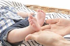 Μητέρα που κρατά το άσπρο υπόβαθρο κινηματογραφήσεων σε πρώτο πλάνο ποδιών ενός χαριτωμένου μωρού στοκ φωτογραφίες