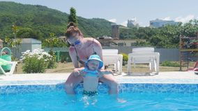 Μητέρα που κρατά το αγοράκι της και αυτός που έχει τη διασκέδαση στην πισίνα φιλμ μικρού μήκους