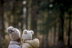 Μητέρα που κρατά το παιδί της και οι δύο που φορούν τα θερμά καπέλα έξω στα fores Στοκ Εικόνα
