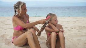 Μητέρα που κτενίζει την τρίχα της κόρης της στην παραλία απόθεμα βίντεο