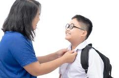 Μητέρα που ντύνει τον ομοιόμορφο σπουδαστή ο γιος της στοκ εικόνες
