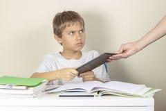 Τηλεοπτικός εθισμός παιχνιδιών Μητέρα που παίρνει την ταμπλέτα μακρυά από τα χέρια παιδιών στοκ εικόνα