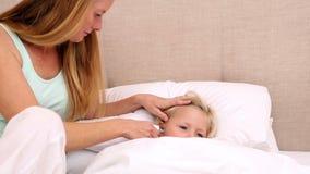 Μητέρα που παίρνει τη θερμοκρασία της άρρωστης κόρης απόθεμα βίντεο