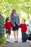 Μητέρα που περπατά στο σχολείο με τα παιδιά στον τρόπο να εργαστεί Στοκ Εικόνες