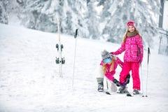Μητέρα που προετοιμάζει την κόρη για να κάνει σκι Στοκ Φωτογραφίες