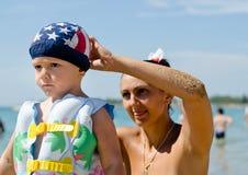 Μητέρα που στερεώνει την κολύμβηση γιων της Στοκ εικόνα με δικαίωμα ελεύθερης χρήσης