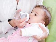 Μητέρα που ταΐζει τη νεογέννητη κόρη με τη σίτιση του μπουκαλιού Στοκ Εικόνα