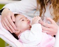 Μητέρα που ταΐζει τη νεογέννητη κόρη με τη σίτιση του μπουκαλιού Στοκ Φωτογραφία
