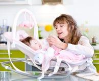 Μητέρα που ταΐζει τη νεογέννητη κόρη με τη σίτιση του μπουκαλιού Στοκ Εικόνες