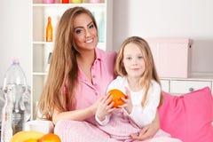 Μητέρα που τρώει τα φρούτα με το παιδί στοκ φωτογραφίες