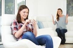 Μητέρα που υποστηρίζει με την κόρη πέρα από τη χρήση του κινητού τηλεφώνου στοκ εικόνα
