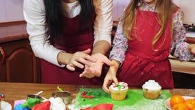 Μητέρα που φιλά την κόρη της κατά τη διάρκεια τους που διακοσμούν cupcake απόθεμα βίντεο