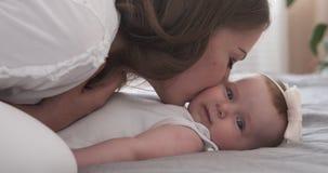 Μητέρα που φιλά το κοριτσάκι της στο κρεβάτι φιλμ μικρού μήκους