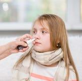 Μητέρα που χρησιμοποιεί τον ψεκασμό μύτης για να θεραπεύσει το κορίτσι εφήβων της στοκ εικόνες