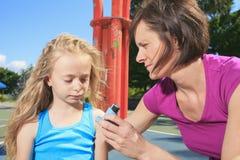 Μητέρα που χρησιμοποιεί inhaler με την ασθματική κόρη της στοκ φωτογραφία
