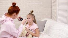 Μητέρα που χύνει το αντιπυρετικό σιρόπι στους αρρώστους λίγο παιδί φιλμ μικρού μήκους
