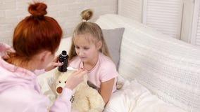 Μητέρα που χύνει το αντιπυρετικό σιρόπι στους αρρώστους λίγο παιδί απόθεμα βίντεο