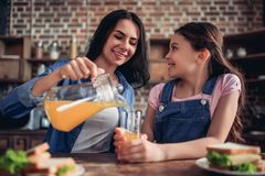 Μητέρα που χύνει το χυμό από πορτοκάλι στο γυαλί στοκ φωτογραφία με δικαίωμα ελεύθερης χρήσης