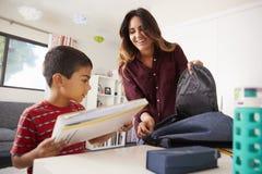 Μητέρα στην κρεβατοκάμαρα που βοηθά το γιο για να συσκευάσει την τσάντα έτοιμη για το σχολείο στοκ εικόνα με δικαίωμα ελεύθερης χρήσης