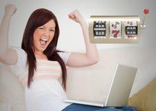 Μηχάνημα τυχερών παιχνιδιών με κέρματα χαρτοπαικτικών λεσχών μπροστά από το παιχνίδι γυναικών στο φορητό προσωπικό υπολογιστή στοκ εικόνα με δικαίωμα ελεύθερης χρήσης