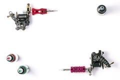 Μηχανές δερματοστιξιών και τρία μπουκάλια του μελανιού που απομονώνεται στο άσπρο υπόβαθρο πυροβόλα όπλα δερματοστιξιών στοκ φωτογραφίες