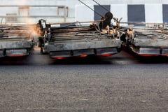 Μηχανή θερμαστρών Serface που λειτουργεί στο δρόμο ασφάλτου Στοκ εικόνα με δικαίωμα ελεύθερης χρήσης