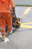 Μηχανή και εργαζόμενος στη χρήση οδοποιίας για τη ζωγραφική σημαδιών δρόμων και κυκλοφορίας Στοκ φωτογραφία με δικαίωμα ελεύθερης χρήσης