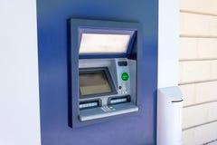 Μηχανή μετρητών του ATM στον τοίχο ενός κτηρίου σε μια οδό πόλεων, που λειτουργεί και λειτουργικό, κανένας άνθρωπος πλησίον στοκ φωτογραφία με δικαίωμα ελεύθερης χρήσης