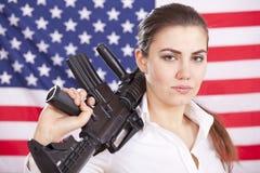 μηχανή πυροβόλων όπλων αμερικανικών σημαιών πέρα από τη γυναίκα Στοκ Εικόνα
